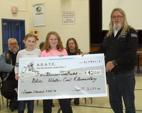 Pictured above, Bluewater Coast Elementary School students Kaitlyn (left) and Emily (right) are presented with the $4,200 by ABATE of Ontario South Huron Chapter 7 president Claude Jones during the school's assembly on Jan. 9. (William Proulx/Exeter Lakeshore Times-Advance)