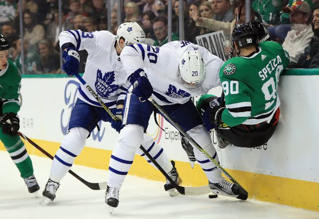 Jason Spezza of the Stars gets knocked to the ice by Leafs Dominic Moore while Travis Dermott collects the loose puck Thursday night in Dallas. (Photo by Ronald Martinez/Getty Images)