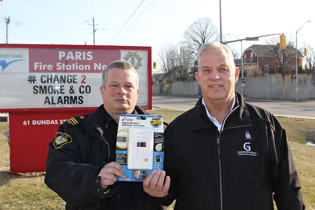 Jeff Balkwill (left), Brant County fire prevention officer, and John Gignac, of the Hawkins-Gignac Foundation, hold with a carbon monoxide detector in front of Brant County Fire Station No.  1 in Paris. They have teamed up on a new program to help keep seniors safe from CO poisoning by distributing and installing detectors in the homes of seniors. (Vincent Ball/The Expositor)