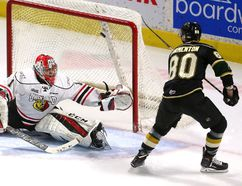Knights forward Alex Formenton flips a rolling puck over the glove hand of Owen Sound Attack goalie Mack Guzda after picking up a perfect end boards bank shot by London defenceman Evan Bouchard to opening the scoring during the first period of their OHL game at Budweiser Gardens on Friday night. The Knights won 7-4. (MIKE HENSEN, The London Free Press)