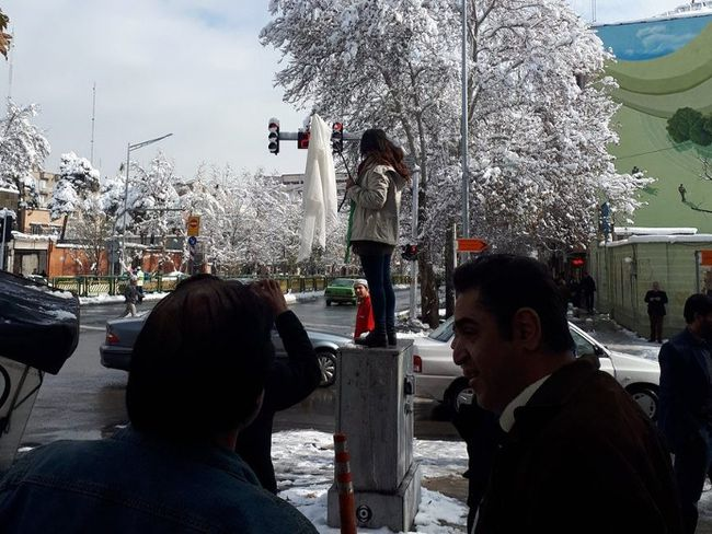 In this photo posted to Twitter, a young woman allegedly in Tehran, Iran waves her headscarf on a stick. @Amiroai / Twitter