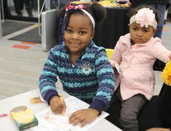 Kendralee Reid, 3, does some colouring while her 16-month-old sister Keneicka looks on at the grand opening on Saturday of the renovated and expanded Delhi branch of the Norfolk County Public Library. MICHELLE RUBY/SIMCOE REFORMER