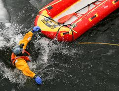 TIM MILLER/The Intelligencer Firefighter Basil Wood jumps into the frigid waters of the Trent River during an ice rescue training session on Wednesday in Trenton.