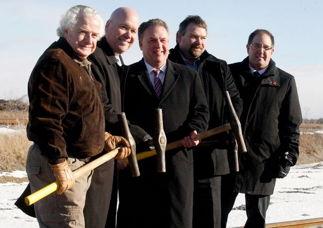 From left, Edwardsburgh/Cardinal Mayor Pat Sayeau, Leeds-Grenville MPP Steve Clark, Leeds-Grenville MP Gord Brown, CREWS president and chief executive officer Clayton Jones and CN sales and marketing official Daniel Lajoie pose after the ceremonial driving of the last spike at Canadian Rail Equipment Works and Services Inc. on Friday. (RONALD ZAJAC/The Recorder and Times)