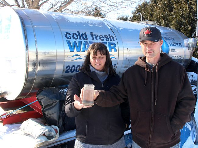 Paul and Jessica Brooks worry about where they will get their water in the future now that the Ministry of Environment and Climate Change has concluded the construction of the North Kent 1 Wind Farm project has not caused the water well to go bad on their home, north of Chatham, Ont. They are seen here on Monday February 5, 2018 in front of a water tank the wind developer is no longer required to provide due to the MOECC ruling. (Ellwood Shreve/Chatham Daily News/Postmedia Network)