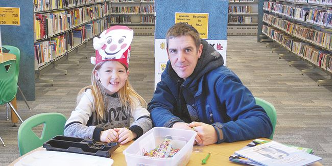Isabel McCauley, 7, and dad, Ryan McCauley take a break from learning about penguins to create some beautiful elastic bracelets. One of the staff members at the library showed Isabel how to make a link bracelet with one of the kits library patrons can sign out at the desk. Allana Plaunt/Special to Sault This Week