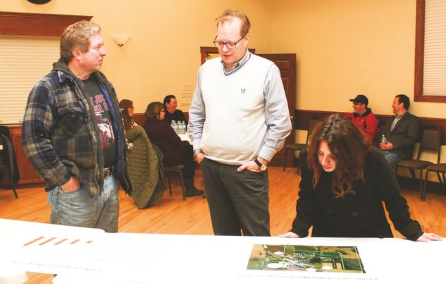 MDB Insight's Harry Shnider speaks with James Phinney during the industrial land open house Jan. 25 at the Vulcan Lodge Hall. Also pictured is Carmen Pelletier, who's looking at a map showing where a potential business park could be located. Jasmine O'Halloran Vulcan Advocate
