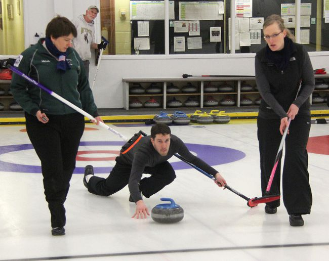 Mike Vosberg of Team Doremus throws a rock as his teammates Amanda Vosberg (right) and Michelle DeBuck get ready to sweep during the second end of the 1st Event Final at the 41st Oil-Chemical Bonspiel in 2014. (File photo)