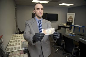 Detective constable Paul Ferreira with counterfeit bank notes recently seized in London, Ont. on Wednesday February 7, 2018. (DEREK RUTTAN, The London Free Press)