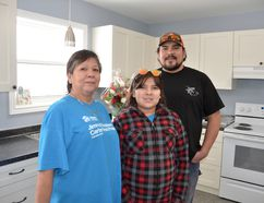 Happy Habitat for Humanity home owner Donna Akiwenzie, with son Jesse and his daughter Chase, 11, who will all live in this new bungalow at Neyaashiinigmiing. They received the keys Saturday. It's the first Habitat build on native land in Ontario. (Scott Dunn/The Sun Times)