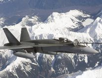 A CF-18 fuels up over the mountains.