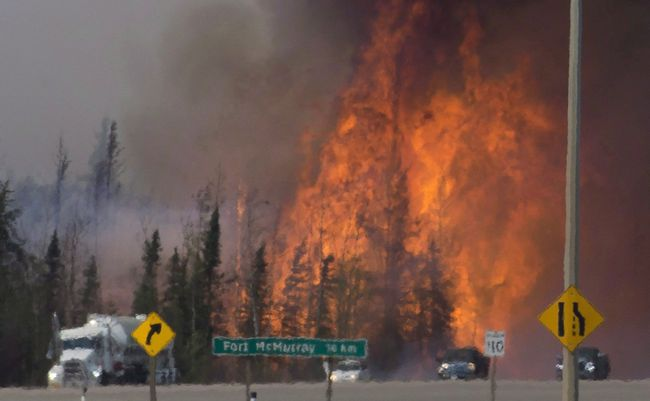 Heat waves are seen as cars and trucks try and get past a wild fire 16 km south of FortMcMurray on Hwy 63 on May 6, 2016.