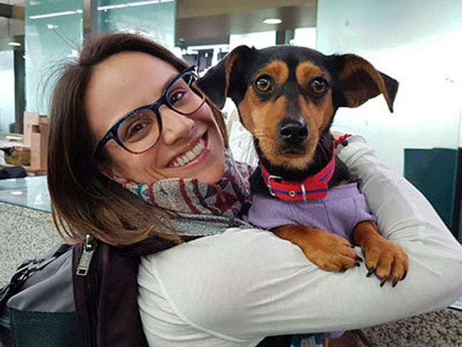 In this undated photo provided by Free Korean Dogs, Canadian figure skater Meagan Duhamel of Lively poses with her dog Moo-tae, right, in South Korea. Duhamel already has one life-changing souvenir from South Korea, and it's not a medal. The Olympic pairs skater rescued a puppy from the Korean dog meat trade while competing in Pyeongchang last year, and she's helping organize more adoptions while skating there at this year's games. (EK Park/Free Korean Dogs via AP)