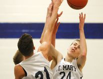 St. Mary Crusaders Connor Kelly (24) and Erik Goodberry (21) jump for the ball during their LGSSAA semifinal game against the St. Michael Mustangs on Tuesday. (Jonathon Brodie/The Recorder and Times)