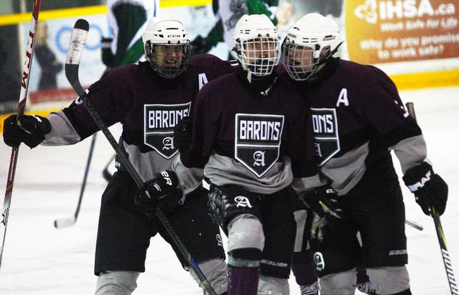 Ryan Fournier (10), of the Algonquin Barons, celebrates his game-winning goal against the West Ferris Trojans with teammates Matthew Cirullo (30), right, and Riley Desjardins (16) at the Sam Jacks Recreation Complex, Thursday. Algonquin won 2-1 to sweep the Trojans in their NDA high school hockey semifnal series after a 4-5 overtime victory Monday. Finals against the Scollard Bears is scheduled to start Feb. 25. Dave Dale / The Nugget