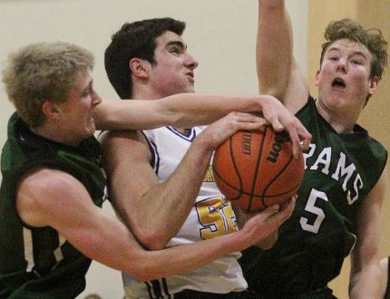 St. Mike's Jack Reilly drives to the net flanked by Stratford Central defenders Derek Delafranier, left, and Evan Falardeau during the Huron-Perth senior boys basketball final Friday. St. Mike's won 44-21. (Cory Smith/The Beacon Herald)