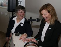 Our TMH board member Sharon Urquhart gets PC leadership hopeful, Christine Elliot, to a sign a Our TMH membership card.