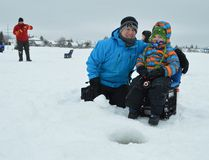 Ty Presseault, 5, didn't catch any fish last year, but he's hopeful for better luck this time around at the Timmins Fur Council's seventh annual family fishing derby. Darin Presseault sits with Ty on Monday morning during a busy event on Porcupine Lake.