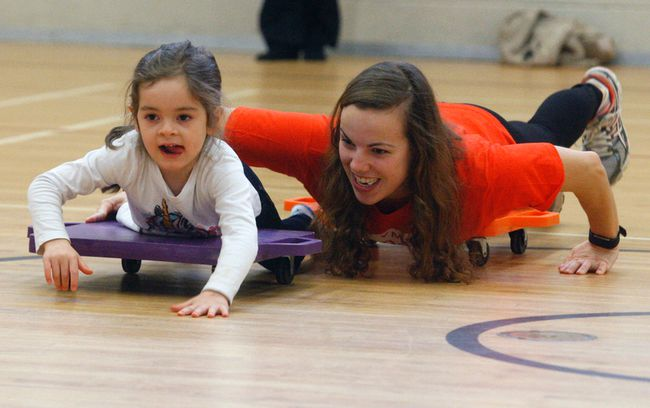 Four-year-old Tessa Miller-Delorme takes part in a bobsled activity with the help of Dorinda Lawlor Monday during the YMCA;s Family Day Games.
