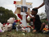 Nekhi Charlemagne writes a message on a cross setup in a makeshift memorial in front of Marjory Stoneman Douglas High School on February 19, 2018 in Parkland, Florida. (Joe Raedle/Getty Images)