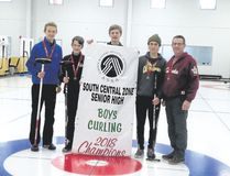 The Canmore Collegiate High School curling team of, left to right, skip Desmond Young, third Ethan Denton, second Ryan Connel and lead Adam Weaterhog, along with coach Dennis Marten pose with the zone curling championship banner on Feb. 13 in Springbank. Photo by Steve Young