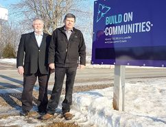 Dutton Dunwich councillor Dan McKillop, left, and Mayor Cameron McWilliam stand beside a Wallacetown water tower project sign. The tower, visible in the background, is undergoing a $448,880 rechlorination system upgrade covered through provincial grants and municipal funds. (Vicki Gough // Special to Postmedia News)