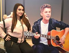 Alexandra Wilson, of Whitby, has her picture taken with Justin Bieber on the Steps of Avon at the Stratford Perth Museum. (Galen Simmons/Postmedia Network )