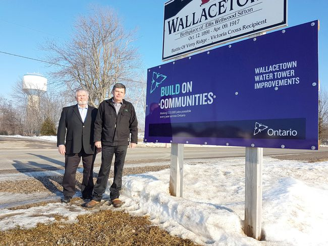 Dutton Dunwich councillor Dan McKillop, left, and Mayor Cameron McWilliam stand beside a Wallacetown water tower project sign. The tower, visible in the background, is undergoing a $448,880 rechlorination system upgrade covered through provincial grants and municipal funds. Vicki Gough/Special to Postmedia News