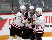 (Left to right) Nick Suzuki celebrates his second period goal with linemates Kevin Hancock and Jonah Gadjovich during the Attack's 7-6 overtime victory in Guelph Friday night against the Storm. Greg Cowan/The Sun Times