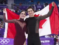 Ice dance gold medallists Canada's Tessa Virtue and Scott Moir hold up the Canadian flag during victory ceremonies at the Pyeongchang Winter Olympics. (THE CANADIAN PRESS)