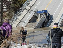 Onlookers gather at the collapsed Imperial Road bridge in Port Bruce on Sunday. The structure gave out while a fully-loaded dump truck was driving across it Friday. (DALE CARRUTHERS / THE LONDON FREE PRESS)