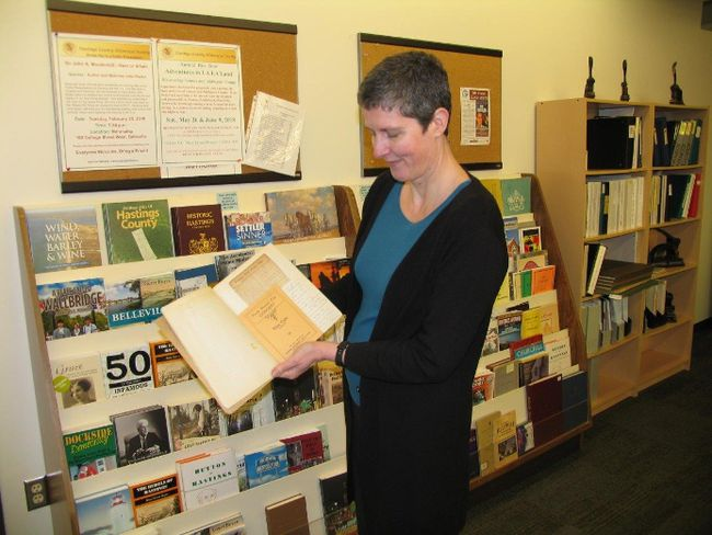 Jack Evans/For The Intelligencer Archivist Amanda Hill studies the minute book of the former Belleville Presto Club in front of a stand of other typical archive items.