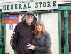 Meghan Balogh/The Whig-Standard David and Linda McGinn stand in front of the Amherst Island General Store in Stella.