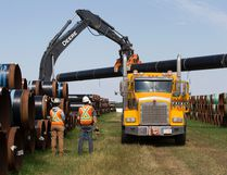 Crews load pipe for Enbridge's Line 3 pipeline replacement project, near Hardisty, Alta., last summer.