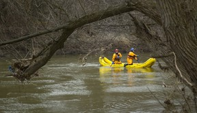 Firefighters use their rescue boats to search the south branch of the Thames River near Vauxhall Park in London, Ont. (MIKE HENSEN, The London Free Press)