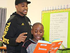 Hamilton Tiger-Cat defensive end Adrian Tracy, with Grade 4 student Noah Olowu, was one of several guest readers at Cedarland School on Wednesday for its Reading Rocks event. (Michelle Ruby/The Expositor)