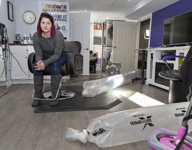 Brian Thompson/The ExpositorSteffany Leggo sits in her salon in the basement of her Birkett Lane home on Friday.. More than a week after the Grand River swelled causing flooding in some areas, fans are still in use to dry the area after pumps ran for five days to remove ground water which flooded her basement.