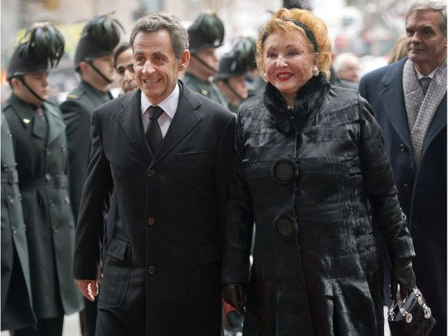 Jacqueline Desmarais, widow of Paul Desmarais, is accompanied by former French president Nicolas Sarkozy as they arrive at a memorial service for Paul Desmarais, Tuesday, December 3, 2013 in Montreal. THE CANADIAN PRESS/Paul Chiasson