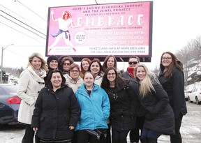Julie Zulich and her employees under a billboard for the movie Embrace, a documentary that promotes positive body image. The film screens at All Nations Church on Tuesday at 7 p.m. (Gino Donato/Sudbury Star)