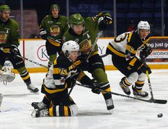 North Bay Battalion defenceman Adam Thilander (3) battles Kingston Frontenacs forward Linus Nyman (75) for a loose puck during first-period Ontario Hockey League action in North Bay Sunday. (Dave Dale/Postmedia Network)