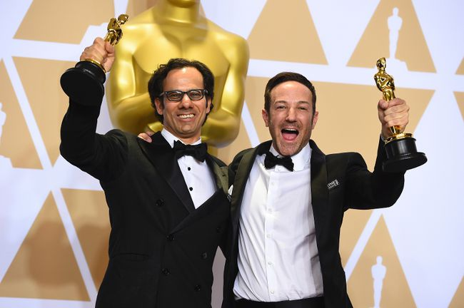 """Dan Cogan, left, and Bryan Fogel, winners of the award for best documentary feature for """"Icarus"""" pose in the press room at the Oscars on Sunday, March 4, 2018, at the Dolby Theatre in Los Angeles. (Photo by Jordan Strauss/Invision/AP)"""