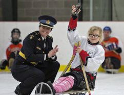 Sixteen-year-old Stacie Ritchie of Brantford hoists her trophy, given to her by Norfolk OPP Insp. Lisa Anderson, following a sledge hockey game on the weekend between South Coast Special Needs Kids team and the police in Waterford. (Brian Thompson/The Expositor)