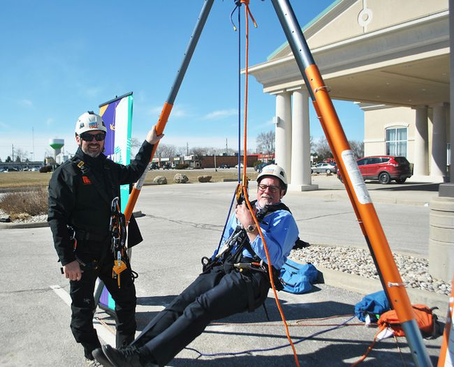 Jim Hogan, CEO of Entegrus, swings from a harness next to Jason McLoughlin, Canadian technical manager of Over the Edge in front of the Holiday Inn Express & Suites on Richmond Street in Chatham Monday. People who raise $1,000 or more in support of the Children's Treatment Centre Foundation of Chatham-Kent will be able to repel down the 10-story hotel June 23. (Tom Morrison/Chatham This Week)