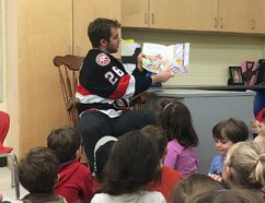 BRUCE BELL/THE INTELLIGENCER Belleville Senator Ben Sexton reads to kindergarten to Grade 2 students at St. Gregory Catholic School in Picton on Tuesday afternoon. Sexton, along with teammates Daniel Ciampini and Marcus Hogberg, dropped into the school for a reading and question-and-answer period.