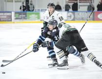 Canmore Eagles captain Trevor Van Steinburg squeezes between two Okotoks Oilers during AJHL action at the Canmore Recreation Centre on Thursday. Pam Doyle/ pamdoylephoto.com