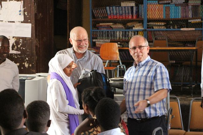 PHOTO SUBMITTED Bruce Beairsto and Chris Andersen speak to students in the city of Jigjiga with books from the Swan City Rotary Club in the background.