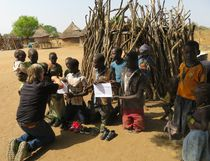 In the countryside near Jebel Lado, Thorndale farmer and volunteer Stuart McCutcheon offers gifts to South Sudanese children. (Supplied)