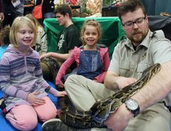 "Zander Ressel of Little Ray's Nature Centre introduces seven-year-olds Harley Emery and Olivia McQueston of Paris to ""Curious George."" a Burmese python, on Saturday at the 16th annual Wildlife Festival and Adventure Show. Michelle Ruby/Postmedia News"