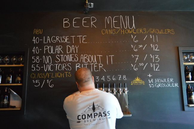 Kevin Patriquin, one of four partners in the newly-opened Compass Brewing, pours beer for a customer on Sunday afternoon.