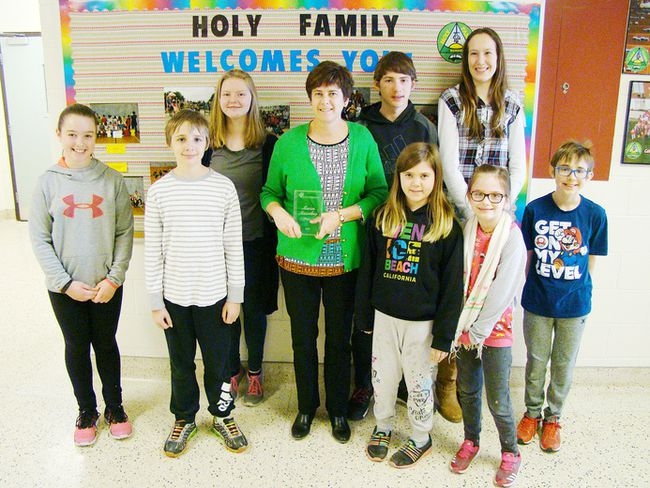 Holy Family School principal Marion Massaloup, centre, displays her Canada's Outstanding Principals award while surrounded by students, front left, Jayden Rahn, Shawn Pierik, Alaina LaPrise, Mia Perkins and Adam Pierik. Back left are Kiara Kunkel, Memphis Fidler-McCarthy and Naomi Gies. (Derek Lester/Postmedia Network)